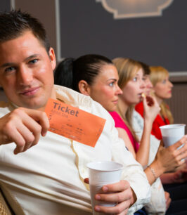 A man in the audience of a theatre, in a concert hall or a cinema presenting a ticket or admission pass